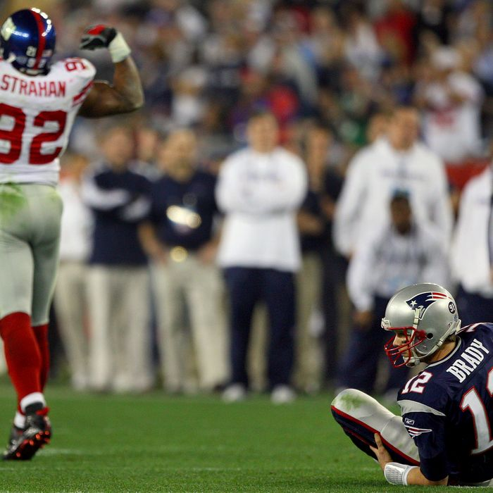 Quarterback Tom Brady gets up off the ground after being sacked by defensive end Michael Strahan