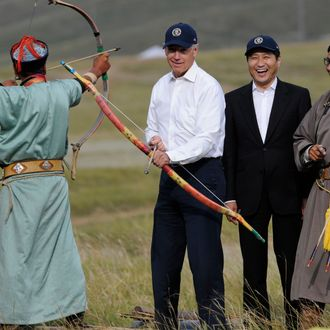 US Vice President Joe Biden (C) tries his hand at archery as Mongolian Prime Minister Sukhbaatar Batbold (2nd R) laughs during a mini Naadam staged in Biden's honour in Ulan Bator on August 22, 2011. Biden on August 22 hailed the United States' growing ties with Mongolia on a rare visit by an American leader to the Asian nation, which is opening up its vast coal reserves to foreign investors. AFP PHOTO / GOH CHAI HIN (Photo credit should read GOH CHAI HIN/AFP/Getty Images)