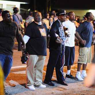 Community leaders join hands and form a barrier between police officers and protesters in attempt to diffuse the escalation between the two, during a peaceful protest in Ferguson, Missouri early on August 20, 2014. Police lowered their profile on August 19, and refrained from using tear gas, to allow a more orderly night of protests in this St Louis suburb 10 days after the police shooting of an unarmed black teenager. AFP PHOTO / Michael B. Thomas (Photo credit should read Michael B. Thomas/AFP/Getty Images)