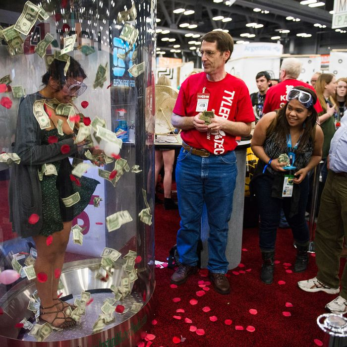 An attendee attempts to grab U.S. one-dollar bills in a promotional booth at the South By Southwest (SXSW) Interactive Festival in Austin, Texas, U.S., on Tuesday, March 11, 2014.