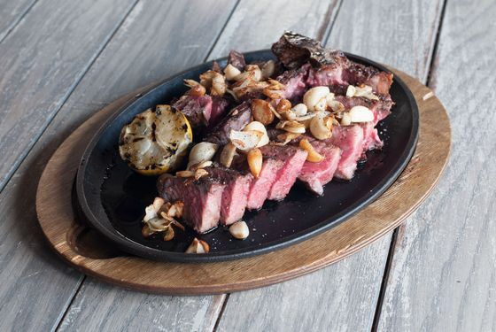 25-day dry-aged beef porterhouse (for three) served sliced, off the bone, with crispy garlic and lemon.