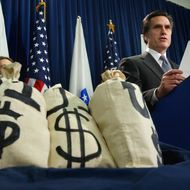 With money bag props at his side, Massachuetts Gov. Mitt Romney reads a bar chart regarding potential changes to the unemployment insurance laws during a news conference at the Statehouse in Boston, Tuesday, Nov. 25, 2003. (AP Photo/Charles Krupa)