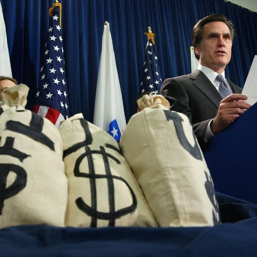 With money bag props at his side, Massachuetts Gov. Mitt Romney reads a bar chart regarding potential changes to the unemployment insurance laws during a news conference at the Statehouse in Boston, Tuesday, Nov. 25, 2003.