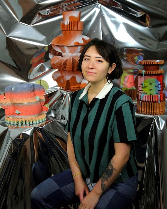 a portrait of a woman with shirt brown hair, a green and black striped shirt posing in front of a group of ceramic vessels and a silver cloth