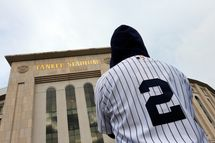 A fan wearing a Derek Jeter jersey stands outside of Yankee Stadium prior to his last game there on September 25, 2014 the Bronx borough of New York City. (Photo by Mike Stobe/Getty Images)