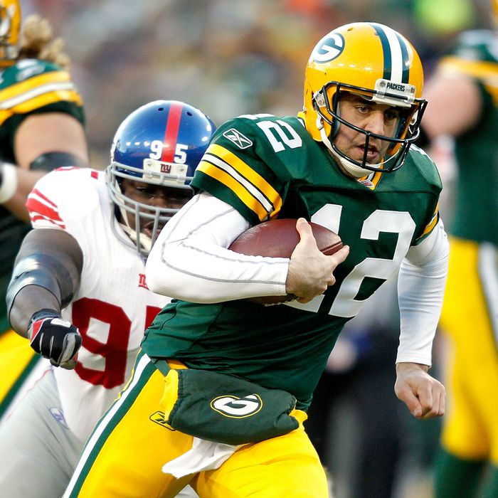 Aaron Rodgers #12 of the Green Bay Packers is chased out of the pocket against the New York Giants at Lambeau Field on December 26, 2010 in Green Bay, Wisconsin.