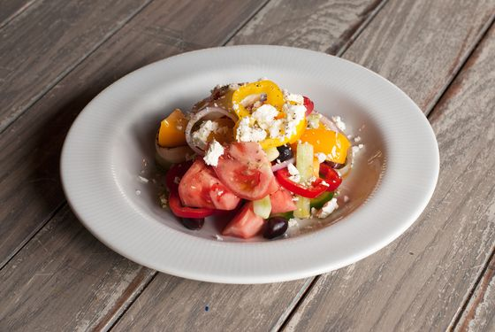 Greek village salad with tomato, cucumber, olives, peppers, feta, and oregano.