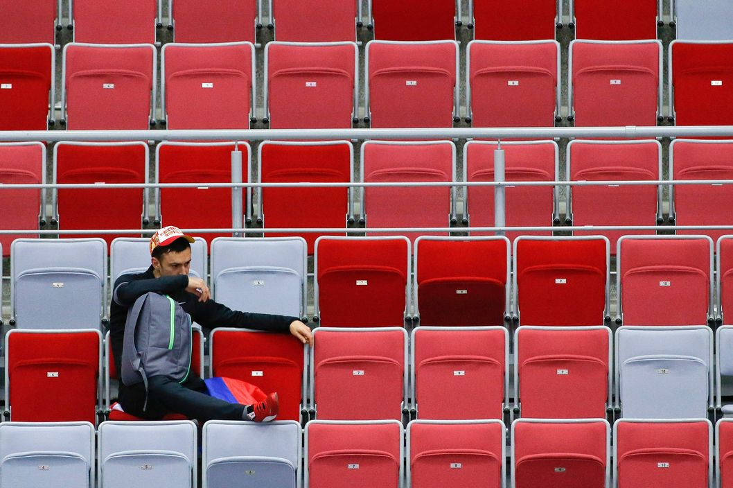 A Russian hockey fan lingers in the seats after Russia lost 3-1 to Finland in a men's quarterfinal ice hockey game at the 2014 Winter Olympics, Wednesday, Feb. 19, 2014, in Sochi, Russia. (AP Photo/Mark Humphrey)