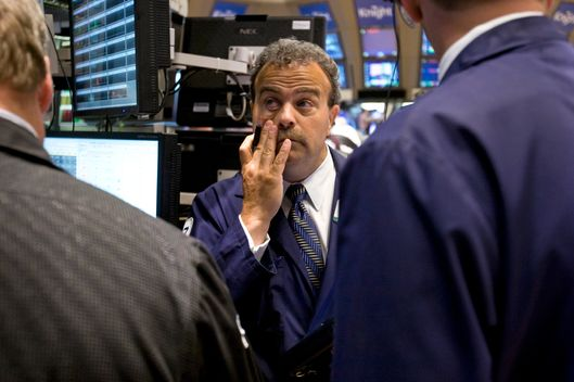 Traders work on the floor of the New York Stock Exchange (NYSE) in New York, U.S., on Monday, Aug. 8, 2011. U.S. stock futures retreated, following the biggest weekly drop in the Standard & Poor's 500 Index since 2008, amid concern that a downgrade of the nation's credit rating by S&P may worsen an economic slowdown. Photographer: Scott Eells/Bloomberg via Getty Images