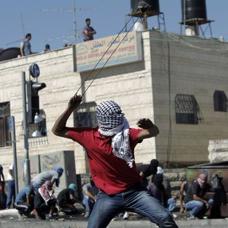 A masked Palestinian protestor uses a sling to throw stones toward Israeli police during clashes in Shuafat neighborhood in Israeli-annexed Arab East Jerusalem, on July 2, 2014, after a Palestinian teenager was kidnapped and killed in an apparent act of revenge for the murder by militants of three Israeli youths.