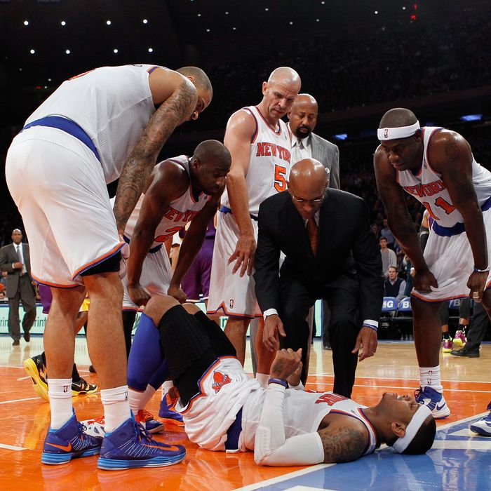 Carmelo Anthony #7 of the New York Knicks lies on the court after being fouled in the game against the Los Angeles Lakers at Madison Square Garden on December 13, 2012 in New York City. Anthony left the game with a sprained ankle. NOTE TO USER: User expressly acknowledges and agrees that, by downloading and/or using this photograph, user is consenting to the terms and conditions of the Getty Images License Agreement. The Knicks defeated the Lakers 116-107.