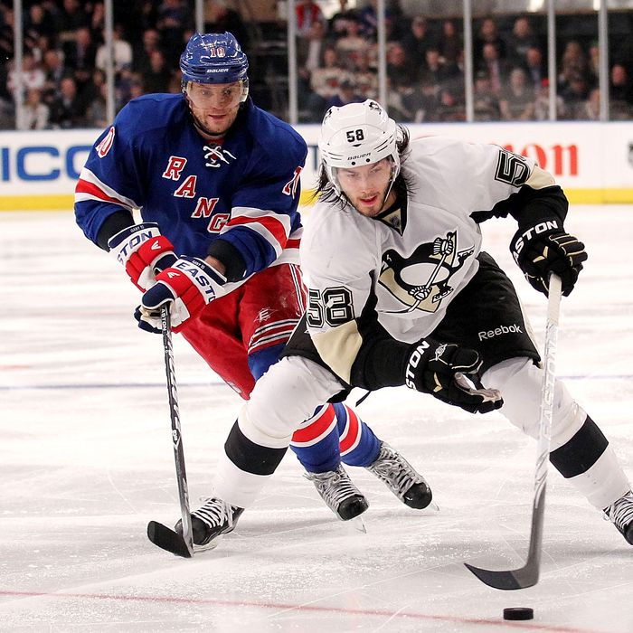 Kris Letang #58 of the Pittsburgh Penguins skates with the puck in front of Marian Gaborik #10 of the New York Rangers