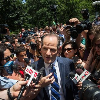 Former New York Gov. Eliot Spitzer is mobbed by reporters while attempting to collect signatures to run for comptroller of New York City on July 8, 2013 in New York City. Spitzer resigned as governor in 2008 after it was discovered that he was using a high end call girl service.
