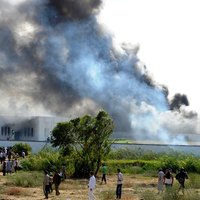 Smoke rises from the burning vehicles at the car park of the US embassy in Tunis during a protest against a film mocking Islam on September 14, 2012. The demonstrators, acting aggressively, managed to clamber over one of the walls round the mission, near the car park where several vehicles had been set ablaze, the photographer said.