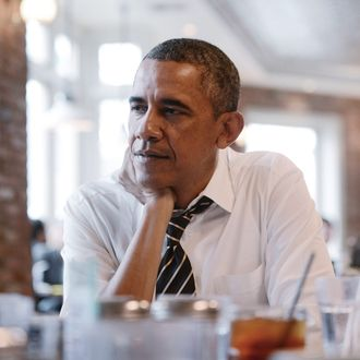 U.S. President Barack Obama listens during a meeting with young citizens at Columbia Height's restaurant The Coupe on January 10, 2014 in Washington, DC.