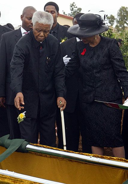 Former South African president Nelson Mandela, accompanied by his wife Graca Machel, throws a rose on the grave of his son Makgatho in his village Qunu in the Eastern Cape. Mandela disclosed that his son had died of AIDS.
