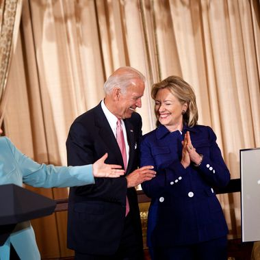 Vice President Joseph R. Biden (C) watches as German Chancellor Angela Merkel (L) presents a front page clipping from the Frankfurter Allgemeine to Secretary of State Hillary Rodham Clinton of their hips during a luncheon at the US State Department June 7, 2011 in Washington, DC.  Secretary of State Hillary Rodham Clinton and Vice President Joseph R. Biden hosted German Chancellor Angela Merkel for a luncheon during her visit to Washington before tonight's State Dinner.