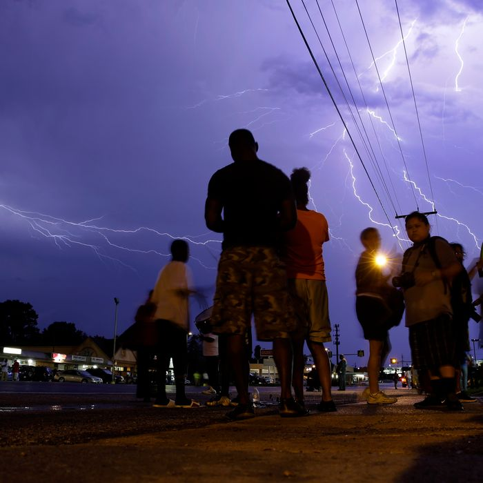 Protesters stand in the street as lightning fills the night sky Wednesday, Aug. 20, 2014, in Ferguson, Mo. A grand jury has begun hearing evidence as it weighs possible charges against the Ferguson police officer who fatally shot 18-year-old Michael Brown. (AP Photo/Jeff Roberson)