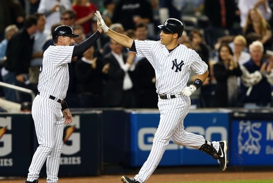 Mark Teixeira #25 of the New York Yankees is congratulated by Rob Thomson #59 as Teixeira rounds third after his home run in the second inning against the Boston Red Sox on October 1, 2012 at Yankee Stadium in the Bronx borough of New York City