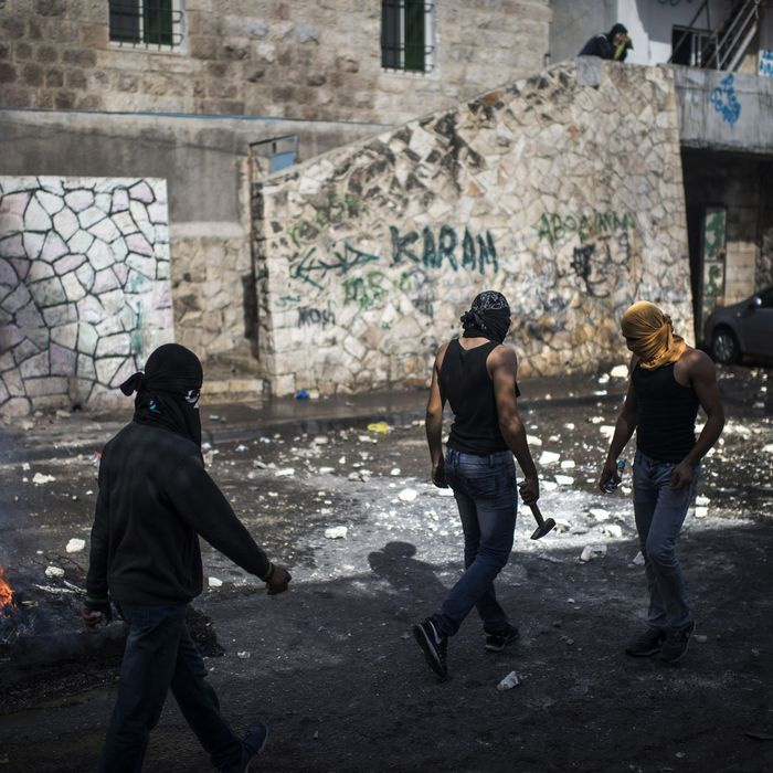 Fire burns near Palestinian youth clashing with Israeli Police on October 30, 2014 in Jerusalem, Israel. Israeli Police was trying to arrest and killed Muataz Hijazi, who was a suspect in shooting of Israeli right wing activist Rabbi Yehuda Glick. Public Security have closed down the Temple Mount to until further notice following the assassination attempt of the right-wing activist.