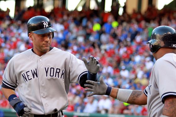 ARLINGTON, TX - APRIL 23:  Derek Jeter #2 of the New York Yankees celebrates a run with Andruw Jones #22 against the Texas Rangers in the first inning at Rangers Ballpark in Arlington on April 23, 2012 in Arlington, Texas.  (Photo by Ronald Martinez/Getty Images)