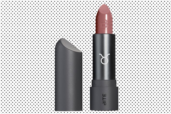 A subtle, muted rosy lipstick shade in a black lipstick tube that has the Taurus symbol on the front