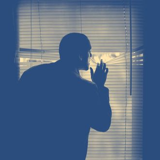 A man peeking outdoors through the blinds of a darkened room