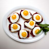 Armenian pastrami (aka basturma) canapés topped with fried quail eggs.