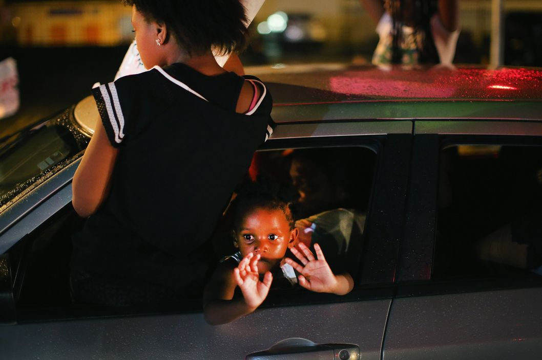 "FERGUSON, MO - AUGUST 15:  A young child looks out from a car as demonstrators drive down West Florissant Avenue protesting the shooting and death of Michael Brown on August 15, 2014 in Ferguson, Missouri. Brown was shot and killed by a Ferguson police officer on August 9. Protestors raise their hands and chant ""Hands up, don't shoot""  as a rally cry to draw attention to reports that stated Brown's hands were raised when he was shot. Tonight demonstration again ended with protestors  clashing with police followed by more looting.  (Photo by Scott Olson/Getty Images)"