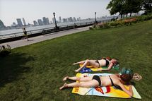 Women sunbathe in Battery Park City on the banks of the Hudson River June 8, 2011 in New York City. An early summer heat wave hit the city with temperatures around 93 degrees today and forecast to hit a record 97 degrees tomorrow.