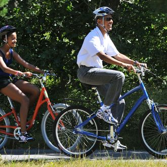 US President Barack Obama rides his bicycle as he is followed by his daughter Malia in West Tisbury on Martha's Vineyard, Massachusetts, on August 27, 2010. The US First Family is vacationing on the island until August 29. AFP PHOTO/Jewel Samad (Photo credit should read JEWEL SAMAD/AFP/Getty Images)