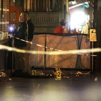 Police (L) investigate the scene of a fatal shooting on W. 58th Street in Manhattan on December 10, 2012 in New York City. A 31-year-old man was shot in the head in the broad daylight and has since been pronounced dead.