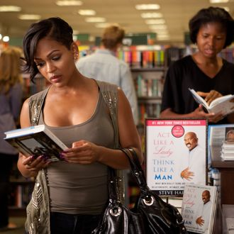 Mya (Meagan Good) grabs a copy of Steve Harvey's book in Screen Gems' comedy THINK LIKE A MAN.