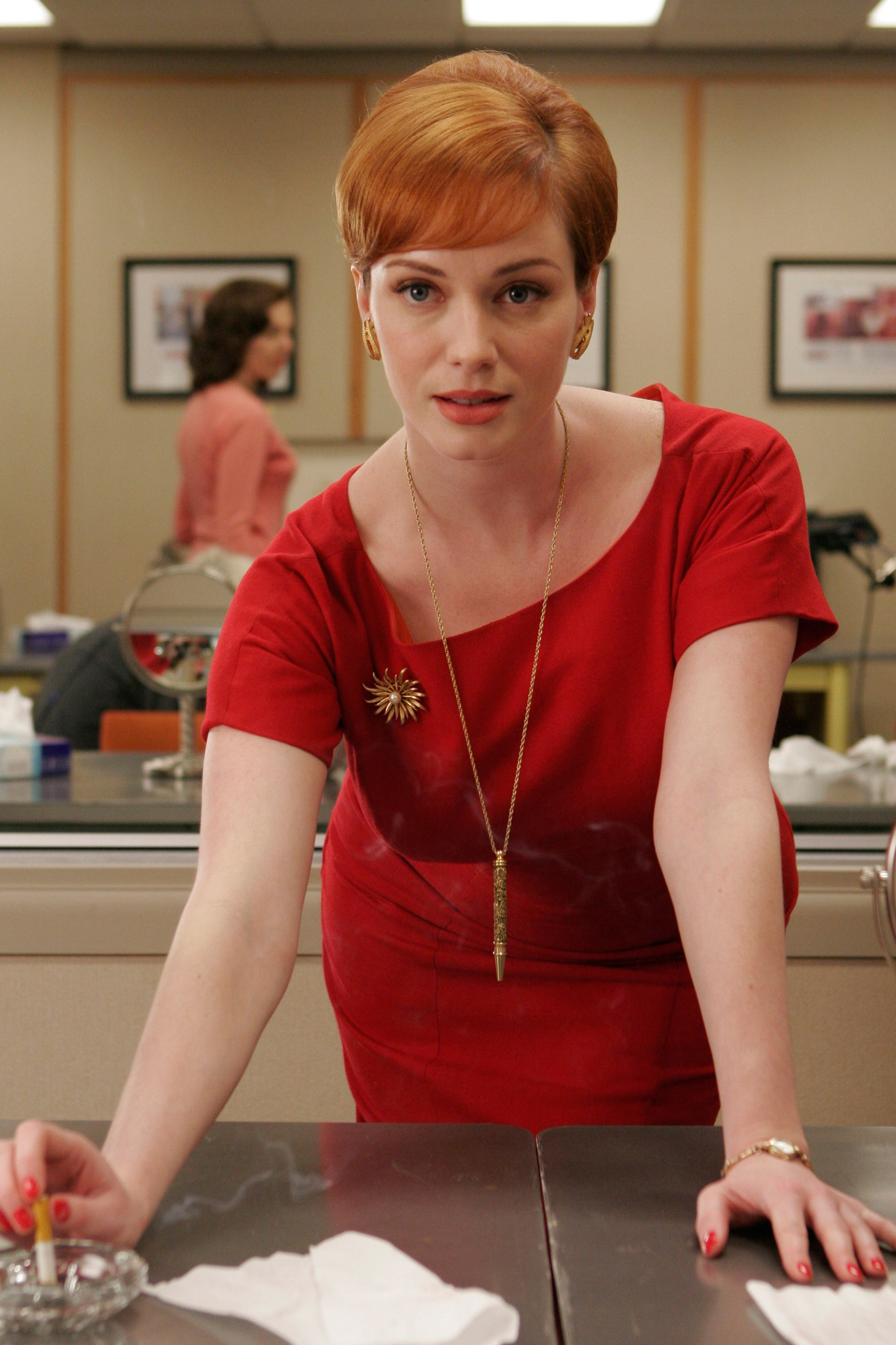 This is the Platonic image of Joan: a snug red sheath topped by her signature pen necklace.
