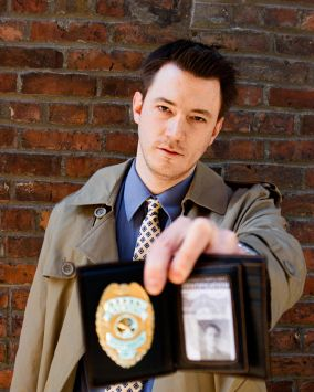 Detective showing his badge and ID (focus on the face, not the badge), a look of routine on his face. Background is a red brick wall. Portrait image on the ID card was shot by me and is available on iStockphoto. An alternative to this image, with the badge in focus is also available.
