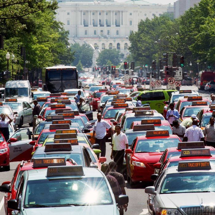 Washington, DC, taxi drivers park their cars and honk the horn in protest on Pennsylvania Avenue, bringing street traffic to a stop as they demand an end to ride sharing services such as Uber X and Lyft on June 25, 2014, in Washington, DC. (Photo credit should read PAUL J. RICHARDS/AFP/Getty Images)