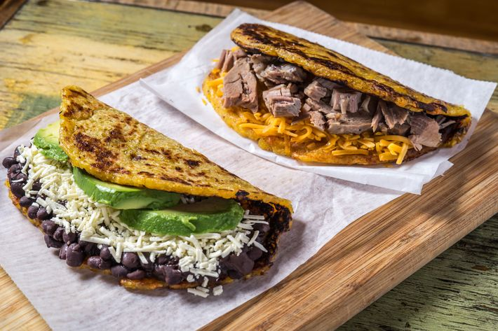 Cachapas, one with roast pork and cheddar and another with beans, shredded white cheese, and avocado.