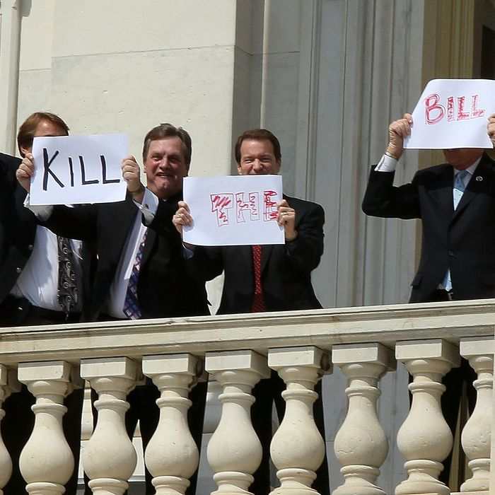 Members of Congress hold up signs from the second floor of the Capitol that read