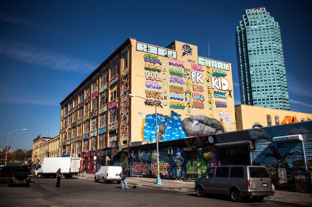 "People stand in front of the 5 Pointz Building, a landmark in the New York graffiti scene that has attracted artists from around the globe, on October 28, 2013 in the Long Island City neighborhood of the Queens borough of New York City. The artists that have been using 5 Pointz to paint for the past two decades are currently in a battle with the building's owners, who want to tear the building down to build apartment high rises worth $400 million. The 5 Pointz artistic community have also called on street artist Banksy who is currently in the midst of a high profile ""month in residence"" series, creating work through out the streets of New York, to weigh in on the battle, though so far the artist has stayed silent. Meres One says he is prepared to chain himself to the building, should demolition move forward."