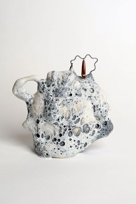 A ceramic vessel with cratery greyish blue glaze that looks like the surface of the moon
