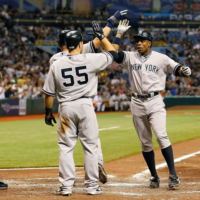 Outfielder Curtis Granderson #14 of the New York Yankees is congratulated by Derek Jeter #2 and Russell Martin #55 after this fifth inning three run home run against the Tampa Bay Rays during the game at Tropicana Field on May 16, 2011 in St. Petersburg, Florida.