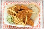 Fried-chicken combo dinners come with rosemary bread, pickled cucumbers, and fries.