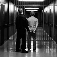 A prison guard leading a prisoner along a corridor