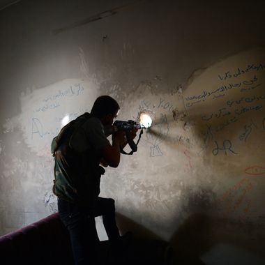 A Syrian rebel observes the movement of regime forces as he takes position inside a building in the Saif al-Dawla district of the northern Syrian city of Aleppo on April 5, 2013. The UN is hiking its estimates of people trapped in Syria after fleeing their homes, saying some four million are now displaced inside the country and in dire need of international help.