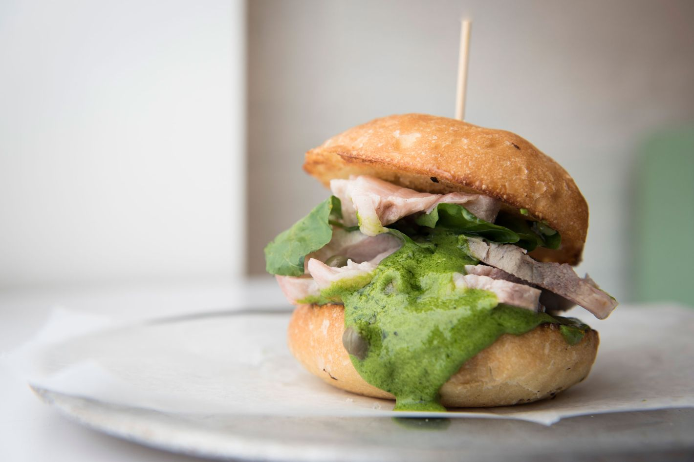 Porchetta-spiced-pork-shoulder sandwich with salsa verde.