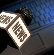 The word News on the side of a broadcast microphone with computer keyboard laptop background for download or podcast or online news concept. Loads of copy space.