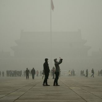 A visitor (centre R) takes a photo in Tiananmen Square during heavy pollution in Beijing on December 1, 2015.