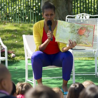 First Lady Michelle Obama reads a book to children during the 2012 White House Easter Egg Roll on the South Lawn of the White House in Washington, DC, April 9, 2012.