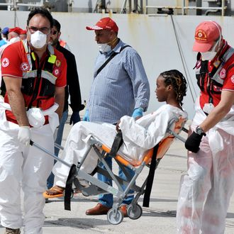 A woman rescued at sea receives medical assistance as the Italian Navy ship