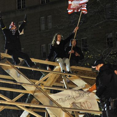 Occupy DC protesters wave to their supporters before their arrest atop a wooden structure at their encampment at McPherson Square in Washington on December 4, 2011. The police moved in to remove the structure the demontrators erected illegally and arrested several protesters. AFP PHOTO/Nicholas KAMM (Photo credit should read NICHOLAS KAMM/AFP/Getty Images)